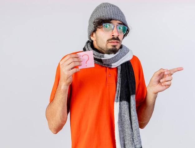 Impressionato giovane indoeuropeo uomo malato con gli occhiali inverno cappello e sciarpa tenendo la nota di domanda guardando la telecamera rivolta verso il lato isolato su sfondo bianco con spazio di copia