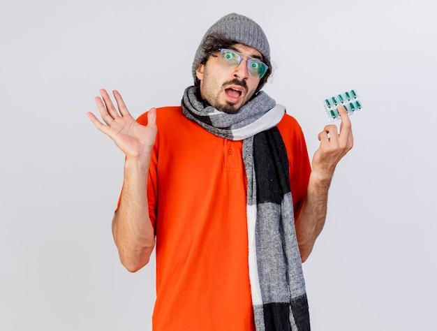 Impressionato giovane indoeuropeo uomo malato con gli occhiali inverno cappello e sciarpa che mostra confezione di capsule e mano vuota isolata sul muro bianco