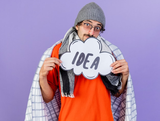 Impressed young caucasian ill man wearing glasses winter hat and scarf wrapped in plaid holding idea bubble  isolated on purple wall