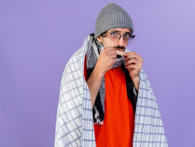 Impressionato giovane uomo malato caucasico con gli occhiali cappello invernale e sciarpa avvolti in plaid che tiene intonaco medico davanti al mento isolato sul muro viola con spazio di copia