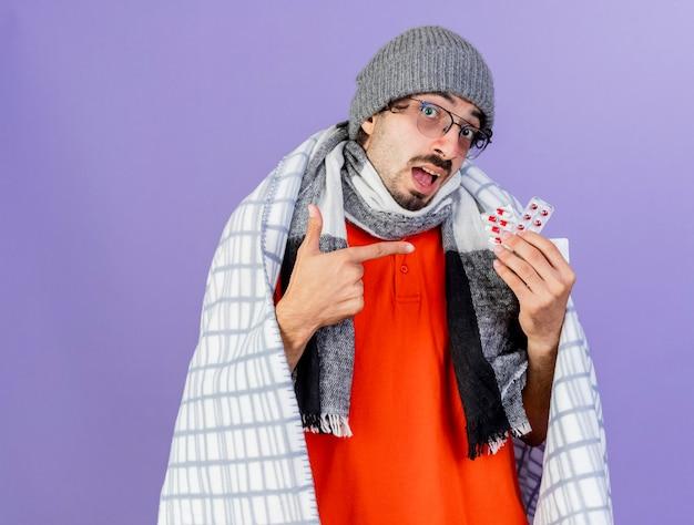 Impressionato giovane uomo malato caucasico con gli occhiali cappello invernale e sciarpa avvolti in plaid tenendo e indicando confezioni di capsule isolate sul muro viola con spazio di copia