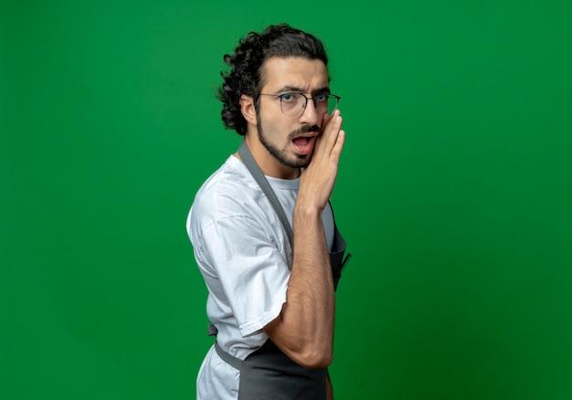 コピースペースで緑の背景に分離されたカメラでささやく口の近くに手を置く制服を着た眼鏡とウェーブのかかった髪のバンドを身に着けている印象的な若い白人男性理髪師