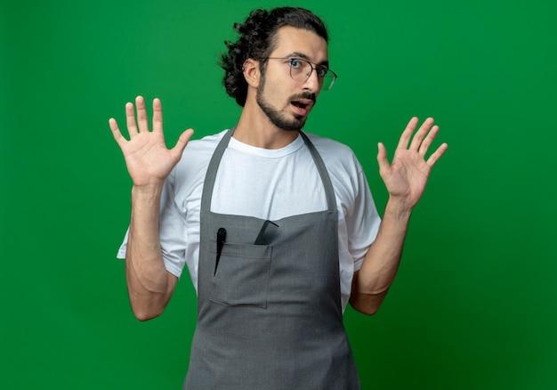 Впечатленный молодой кавказский парикмахер в очках и с волнистой лентой для волос в униформе, показывающий пустые руки