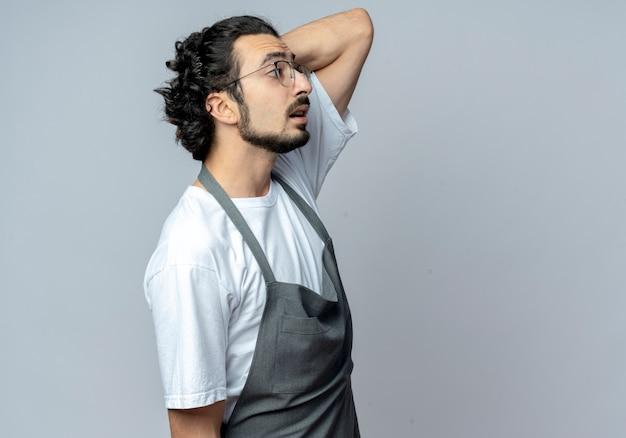 Впечатленный молодой кавказский парикмахер в очках и с волнистой лентой для волос в униформе, стоящий в профиль и смотрящий прямо с рукой за головой
