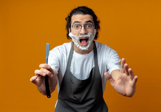 Впечатленный молодой кавказский парикмахер в очках и с волнистой лентой для волос в униформе протягивает опасную бритву и кладет на лицо руку с кремом для бритья