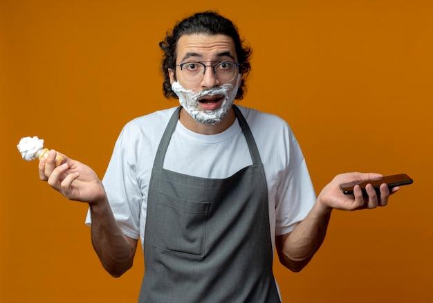 Impressionato giovane barbiere maschio caucasico con gli occhiali e fascia per capelli ondulati in uniforme che tiene pennello da barba e telefono cellulare con crema da barba messo sul suo viso isolato su priorità bassa arancione