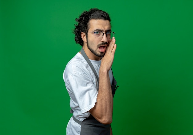 Impressionato giovane barbiere maschio caucasico con gli occhiali e fascia per capelli ondulati in uniforme mettendo la mano vicino alla bocca sussurrando alla telecamera isolata su priorità bassa verde con lo spazio della copia