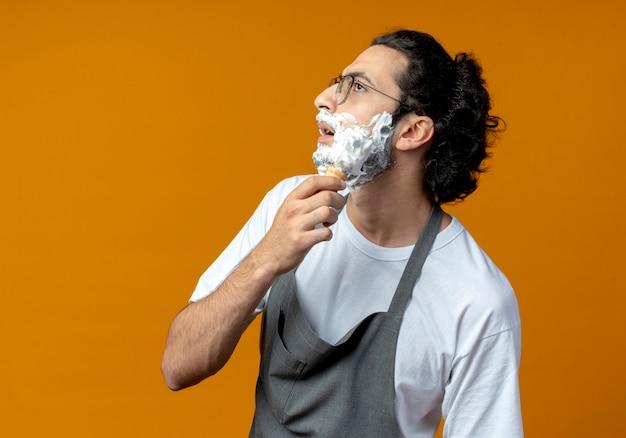 Impressionato giovane barbiere maschio caucasico con gli occhiali e fascia per capelli ondulati in uniforme che mette crema da barba sulla sua barba guardando dritto isolato su sfondo arancione con spazio di copia