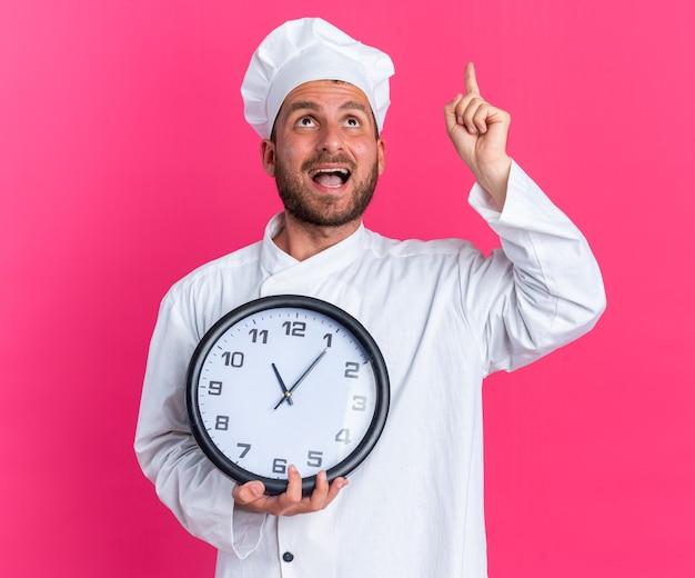 Impressionato giovane cuoco maschio caucasico in uniforme da chef e berretto con orologio che guarda e punta verso l'alto isolato su una parete rosa