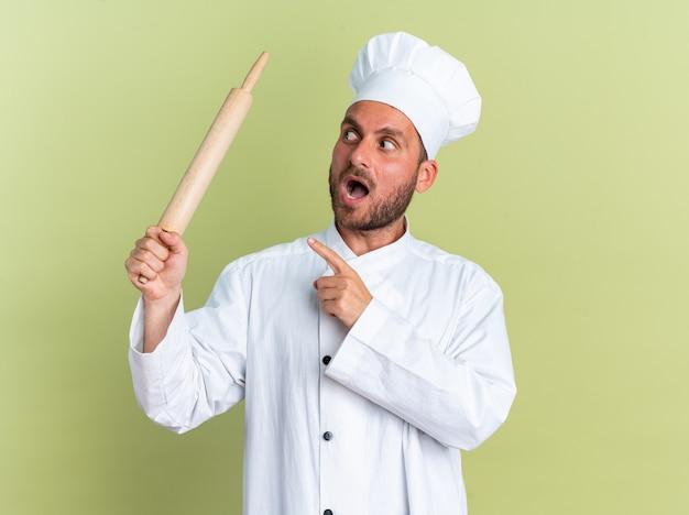 요리사 유니폼을 입은 젊은 백인 남성 요리사와 모자를 들고 롤링 핀을 가리키고 바라보는 것에 깊은 인상을 받았습니다.