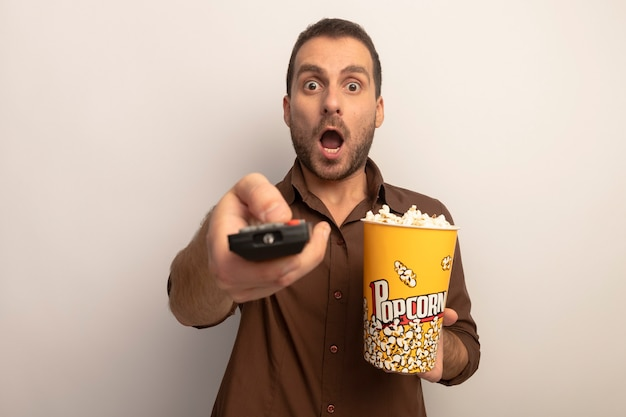 Impressionato giovane uomo caucasico tenendo la benna di popcorn e allungando il telecomando verso la telecamera guardando la telecamera isolata su sfondo bianco con spazio di copia