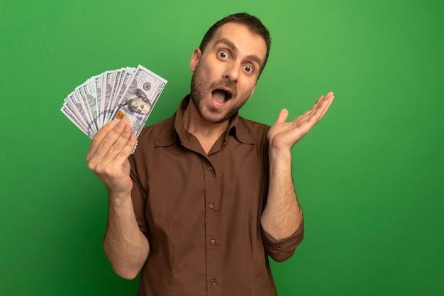 Impressionato giovane uomo caucasico che tiene i soldi che mostrano la mano vuota isolata sulla parete verde con lo spazio della copia