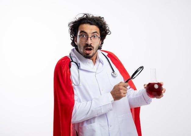 Colpito il giovane uomo caucasico in vetri ottici che indossa l'uniforme del medico con mantello rosso e con lo stetoscopio intorno al collo tiene la lente d'ingrandimento e il liquido chimico rosso nel pallone di vetro