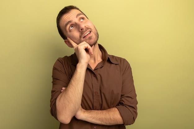 올리브 녹색 배경 복사 공간에 고립 찾고 턱에 손을 넣어 감동 된 젊은 백인 남자