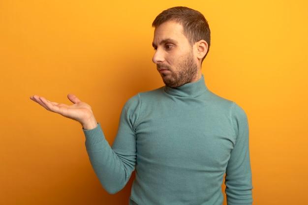 Impressionato giovane uomo caucasico che mostra la mano vuota guardandolo isolato sulla parete arancione