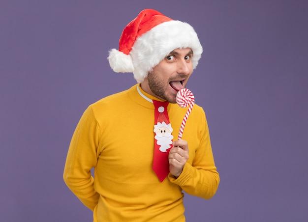 クリスマスの帽子をかぶり、クリスマスの甘い杖を持ったネクタイを着た若い白人男性が、後ろに別の杖を隠し、紫色の壁に隔離された杖を食べる準備をしている舌を見せている