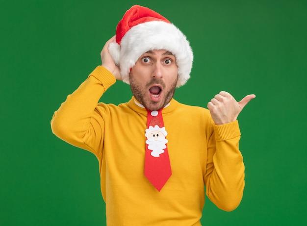 Впечатленный молодой кавказский мужчина в рождественской шляпе и галстуке, держащий руку за голову, смотрит в камеру, указывая на сторону, изолированную на зеленом фоне