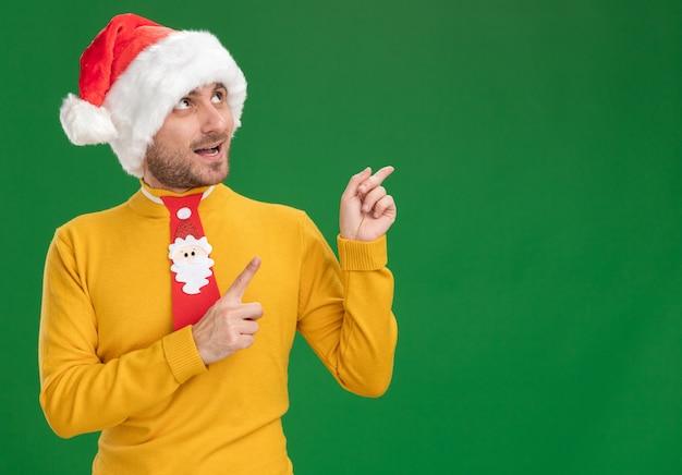 Впечатленный молодой кавказский мужчина в новогодней шапке и галстуке смотрит и указывает вверх изолирован на зеленом фоне