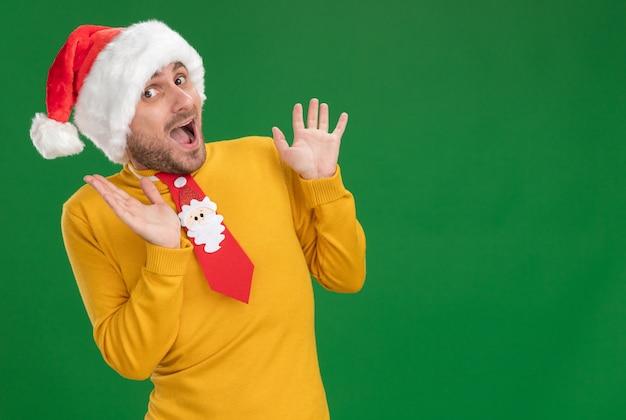 녹색 배경에 고립 된 공기에 손을 유지하는 카메라를보고 크리스마스 모자와 넥타이를 착용하는 감동 된 젊은 백인 남자