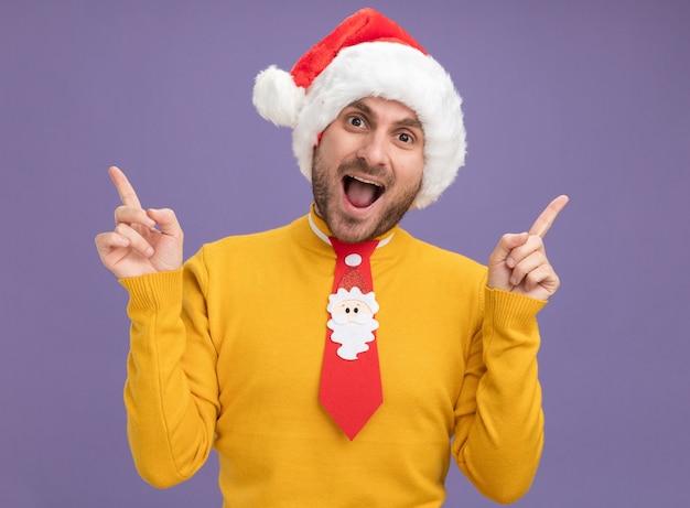 Впечатленный молодой кавказский мужчина в новогодней шапке и галстуке смотрит в камеру, направленную вверх, изолированную на фиолетовом фоне