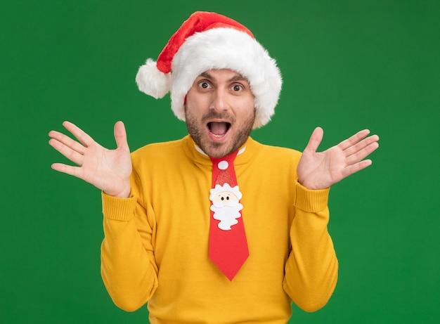 Впечатленный молодой кавказский мужчина в рождественской шляпе и галстуке, глядя в камеру, показывая пустые руки, изолированные на зеленом фоне