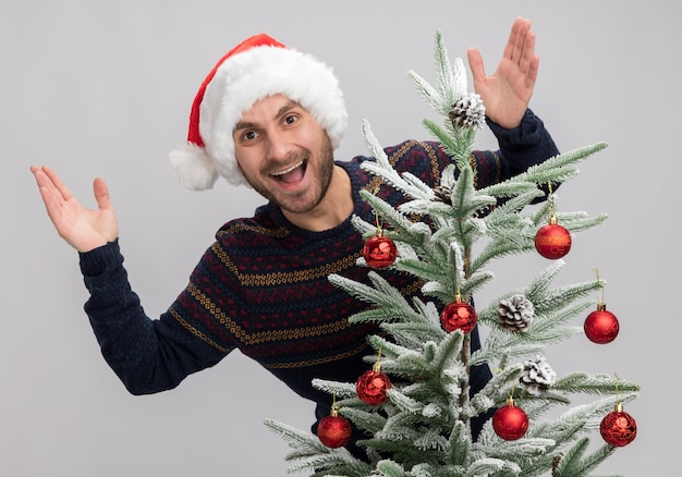 Impressed young caucasian man wearing christmas hat standing behind christmas tree looking at camera keeping hands in air isolated on white background