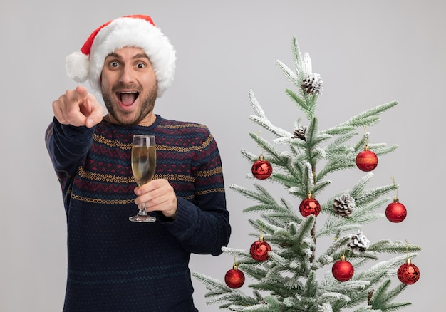 Impressed young caucasian man wearing christmas hat standing near christmas tree holding glass of champagne looking and pointing at camera isolated on white background