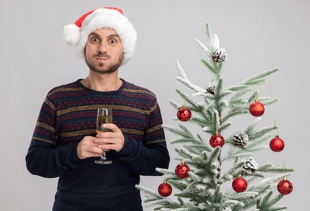 Impressionato giovane uomo caucasico che indossa il cappello di natale in piedi vicino all'albero di natale che tiene un bicchiere di champagne sbuffando guance isolate sul muro bianco