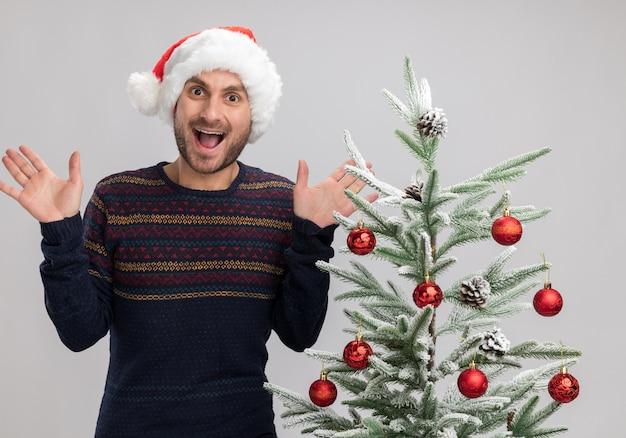 白い背景で隔離の空の手を示すカメラを見てクリスマスツリーの近くに立っているクリスマス帽子をかぶって感動した若い白人男性