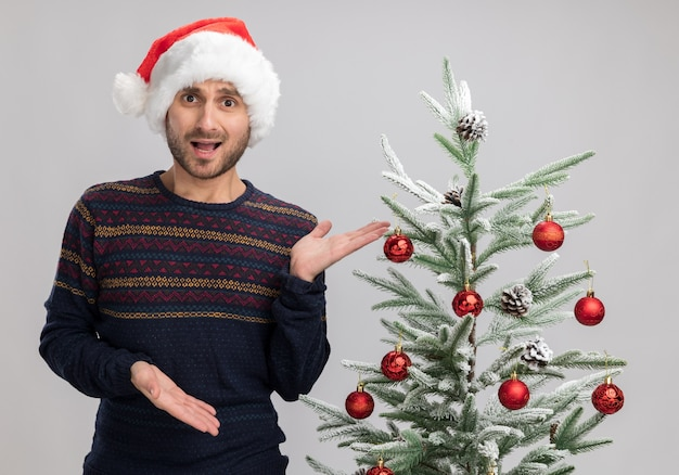 Impressed young caucasian man wearing christmas hat standing near christmas tree looking at camera pointing with hands at tree isolated on white background