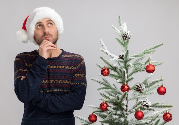 Impressed young caucasian man wearing christmas hat standing near christmas tree touching chin looking up isolated on white background