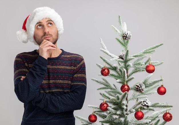 Impressionato giovane uomo caucasico che indossa il cappello di natale in piedi vicino all'albero di natale toccando il mento che osserva in su isolato sul muro bianco