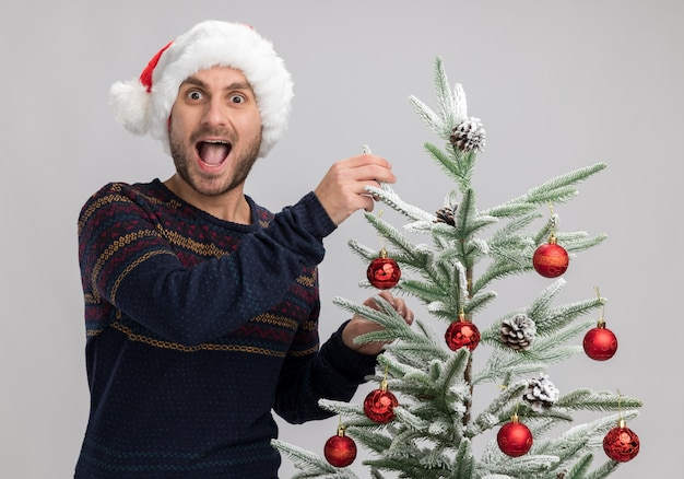 Impressed young caucasian man wearing christmas hat standing near christmas tree touching it looking at camera isolated on white background