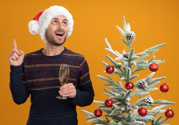 Impressed young caucasian man wearing christmas hat standing near decorated christmas tree holding glass of champagne looking and pointing up isolated on orange background