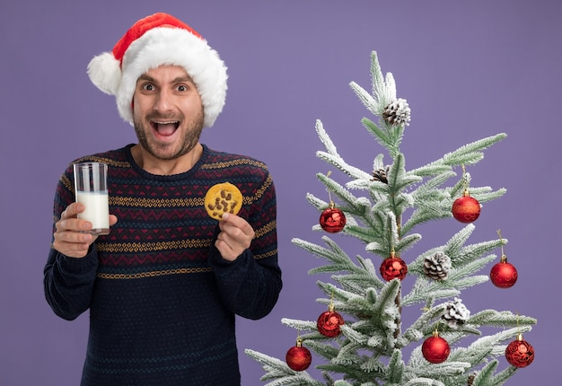Impressed young caucasian man wearing christmas hat standing near decorated christmas tree holding glass of milk and cookie looking at camera isolated on purple background
