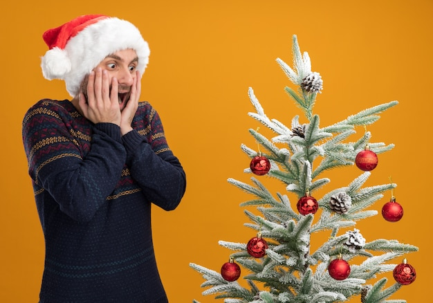 Impressed young caucasian man wearing christmas hat standing near decorated christmas tree keeping hands on face looking at tree isolated on orange background