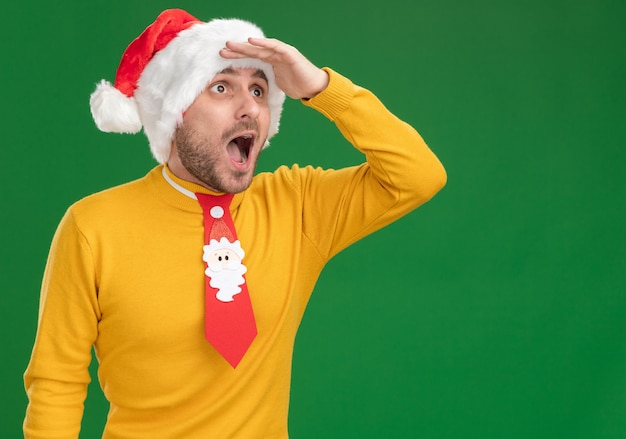 Impressed young caucasian man wearing christmas hat and tie keeping hand on forehead looking at side into distance isolated on green background