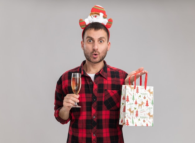 Impressed young caucasian man wearing christmas headband holding christmas gift bag and glass of champagne looking at camera isolated on white background