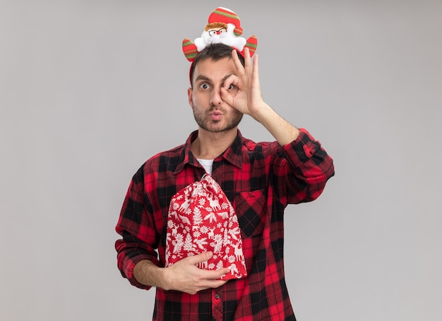 Впечатленный молодой кавказский мужчина в рождественской повязке на голову, держащий рождественский мешок, смотрит в камеру и делает жест со сжатыми губами на белом фоне