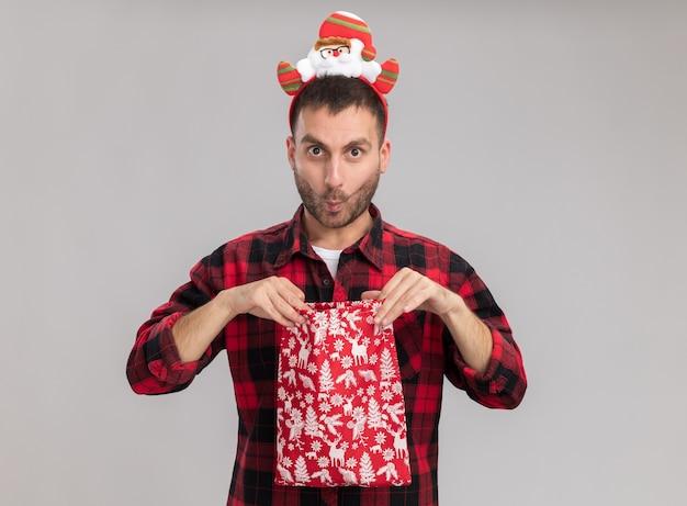 Впечатленный молодой кавказский мужчина в рождественской повязке на голову держит рождественский мешок, открывая его, глядя в камеру со сжатыми губами, изолированными на белом фоне