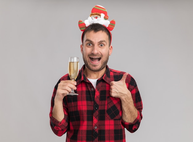 Impressed young caucasian man wearing christmas headband holding glass of champagne looking at camera showing thumb up isolated on white background
