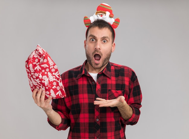 Impressed young caucasian man wearing christmas headband holding and pointing with hand at christmas sack looking at camera isolated on white background