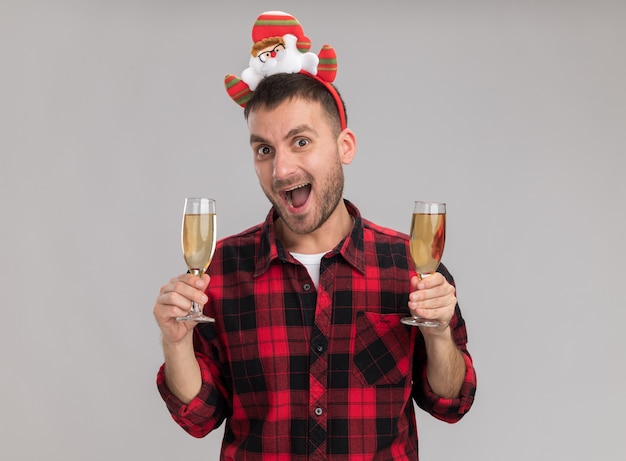 Impressed young caucasian man wearing christmas headband holding two glasses of champagne looking at camera isolated on white background