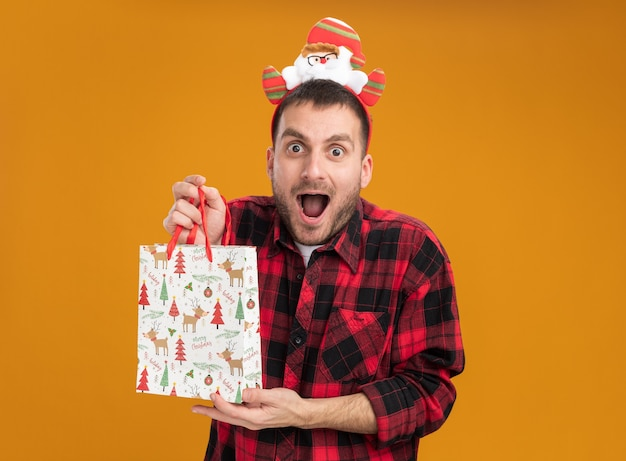 Impressed young caucasian man wearing santa claus headband holding christmas gift bag looking at camera isolated on orange background
