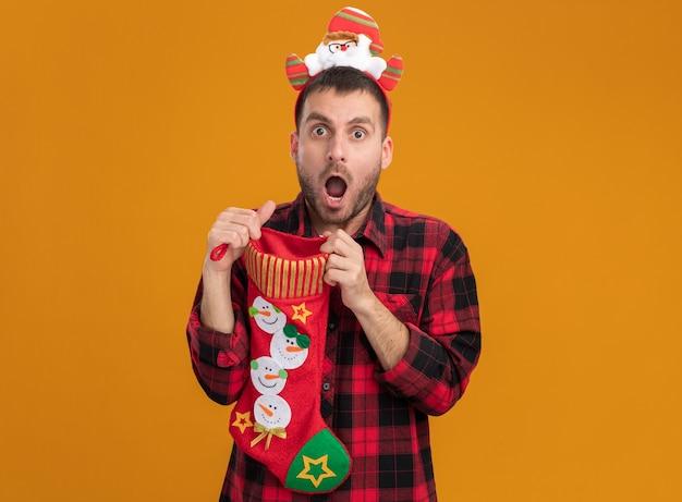 Впечатленный молодой кавказский мужчина в головной повязке санта-клауса держит рождественский чулок, открывая его, глядя в камеру, изолированную на оранжевом фоне
