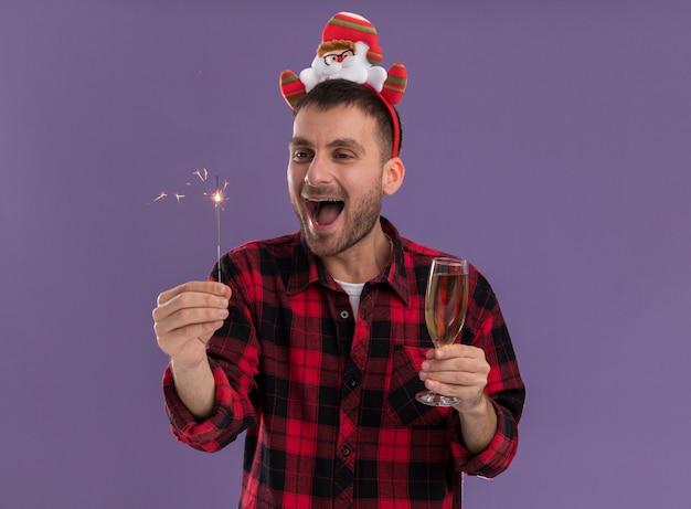 紫色の背景に分離された線香花火を見て休日の線香花火とシャンパングラスを保持しているサンタクロースのヘッドバンドを身に着けている感動の若い白人男性