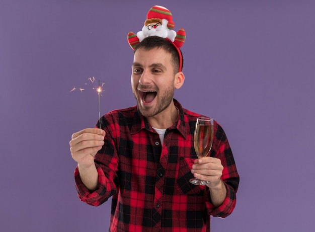 Impressed young caucasian man wearing santa claus headband holding holiday sparkler and glass of champagne looking at sparkler isolated on purple background