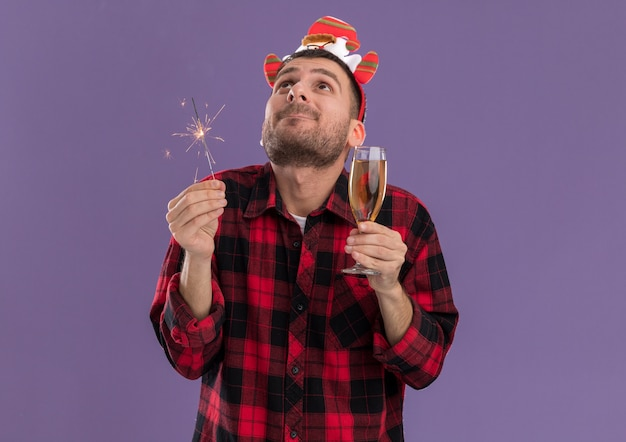 Impressed young caucasian man wearing santa claus headband holding holiday sparkler and glass of champagne looking up isolated on purple background