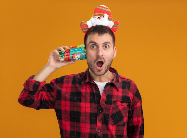 오렌지 배경에 고립 된 카메라를보고 귀 옆에 플라스틱 크리스마스 컵을 들고 산타 클로스 머리띠를 입고 감동 젊은 백인 남자