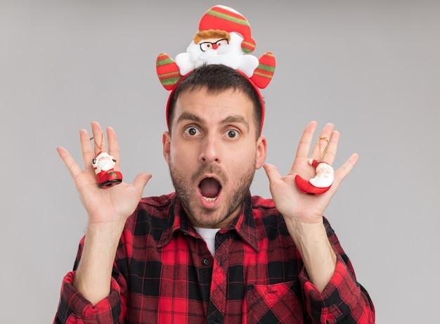 白い背景で隔離のカメラを見てサンタクロースのクリスマスの飾りを保持しているサンタクロースのヘッドバンドを身に着けている印象的な若い白人男性